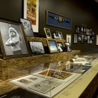Installation view showing display case with photos and papers.