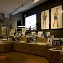 Exhibition interior showing framed photographs of boxers, posters and a screen on the wall.