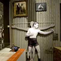 Wall lined with corrugated iron and cut out figures of boxers.