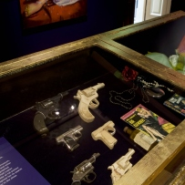 Exhibition display case showing a range of guns.