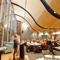 Person presenting at podium to audience under curved wooden ceiling.