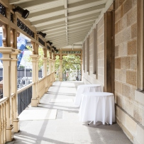 Sunny verandah along side of sandstone building.