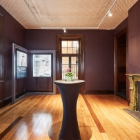 Wooden floored exhibition space with cocktail table set up in centre.