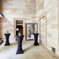Sandstone foyer with cocktail tables set up for event.