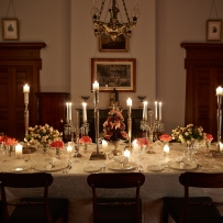 Dining table set for event with lit candles.