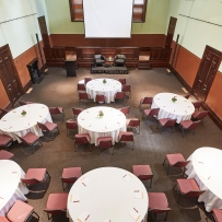 Old style courtroom set up for dining with round tables.