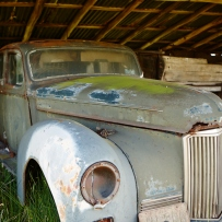 Old disused car in rustic shed.