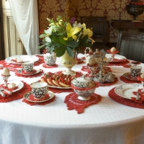 Red doilies sit under a formal 19th century tea set