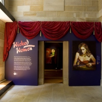 A red curtain hangs over the entranceway to the wicked woman exhibition. A text panel sits to the left of the door while a portrait of Tara Moss hangs to the right.