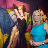 Skye Leckie wearing a blue dress and standing in front of her portrait She Couldn't be Good, at the opening of Wicked Women: an exhibition by Rosemary Valadon