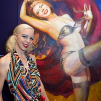 Imogen Kelly stands in front of her portrait