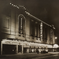 B&W image of theatre at night. An illuminated sign 'REGENT' hangs vertically at the front of the building.