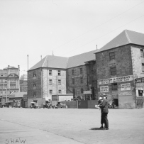 B&W image of U shape Commissariat building. Company signs appear on the walls of the building