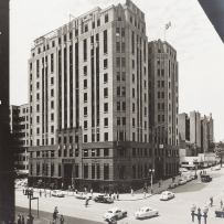 B&W image of a building approximately 12 storeys high, on a street corner. A flag is flying over the building. Cars and pedestrians appear in the streets.
