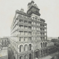 B&W image of a 7 storey building. Balustrades and balconies feature on the building facade.