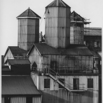 B&W image of a group of engineering unit buildings that feature corrugated roofs and exterior walls. External stairs are attached to one of the buildings.
