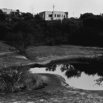 Black and white photo of house and its reflection in a puddle.