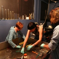 Group of people working with glass plates at wooden bench.