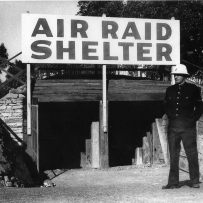AIR RAID SHELTER sign above entrance, with uniformed man to right.