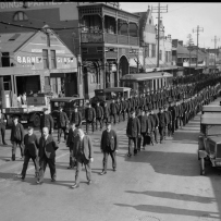 Men in uniforms form two lines as far as the eye can see in a parade down a city street.