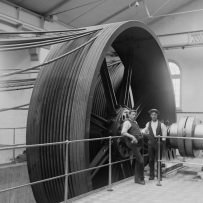 Two men stand beside an enormous steel wheel pulling steel cables.