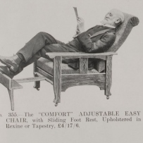 Photo of a man with a grey beard leaning back in a chair reading the paper. The chair has a timber contraption extending out to be used as a foot stool.