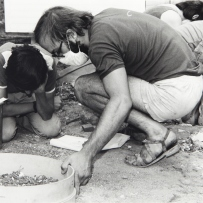 Two men crouching over sieve