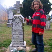 Young boy in striped top standing next to marble tombstone and grave with cross on top