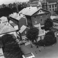 B/W photograph of the Hyde Park Barracks in the 1960s with its courtyard filled with a jumble of poorly built offices and makeshift sheds.