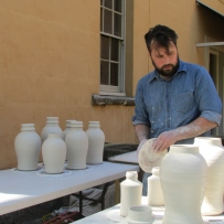 Artist in residence in blue shirt arranges freshly turned ceramic vessels on tables to dry