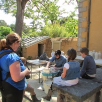 Artist in residence at work on the potters wheel in the stone walled courtyard of vaucluse house