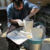 man turning white ceramic vessel on potters wheel