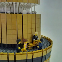 LEGO minifig people stand on top of model tower