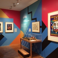 Colourful wall forms backdrop to display cases and fixed iPad.
