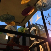 This is a photograph showing exhibition designer Matt Guzowski on a scissor life hanging colourful parasols with light filtering through them from the glass panels
