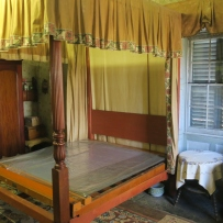 Interior view of bedroom, showing bedcovers being removed for cleaning.