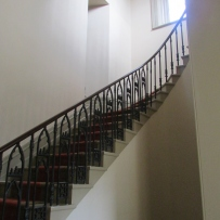 Looking up flight of stairs with black balustrade.