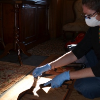 Woman wearing gloves and mask cleaning carpet by hand.