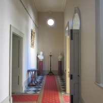 Looking down hallway with red runner and furniture.