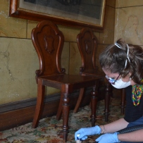 Woman wearing gloves and mask cleaning carpet with two chairs in background.