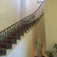 Looking up stairs with black balustrade.