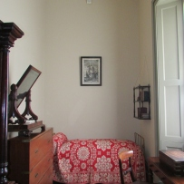 Narrow hallway room with bed and other furnishings.