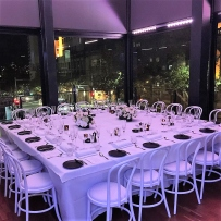 Square dinner table set for event in glasswalled room.