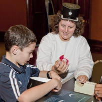 Zac and his mum make a cardboard Kepi cap at the colonial police hat making activity in the Water Police Court, Justice and Police Museum.