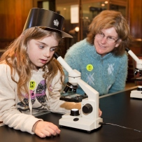 Janet and Anika examining hair samples through a microscope in the Water Police Court, Justice and Police Museum