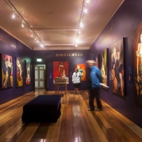Interior view of exhibition space showing purple walls with a range of paintings hung on them.