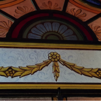 Section of the multi coloured stained glass doors of The mint, which shows a garland with Acanthus leaves watermarked in the background