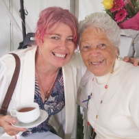 Two women, one younger with pink hair and coffee cup, left, and one older with white hair, right.