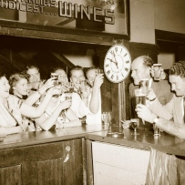 Patrons, drinks raised, crowd a pub bar with a clock showing 10 pm.