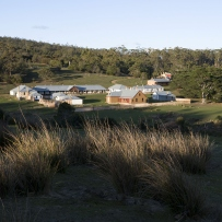 Colour photo showing a compound of low buildings set within a grassy paddocks, surrounded by bushland.